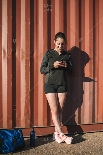 Woman leaning on container and using smartphone