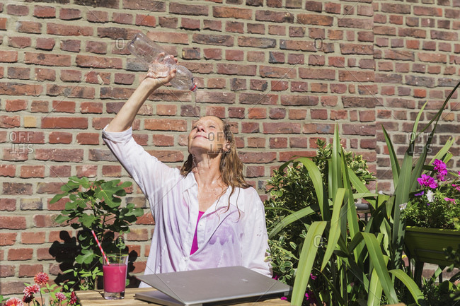 Businesswoman refreshing herself by pouring water from bottle at balcony against brick wall during break on sunny day
