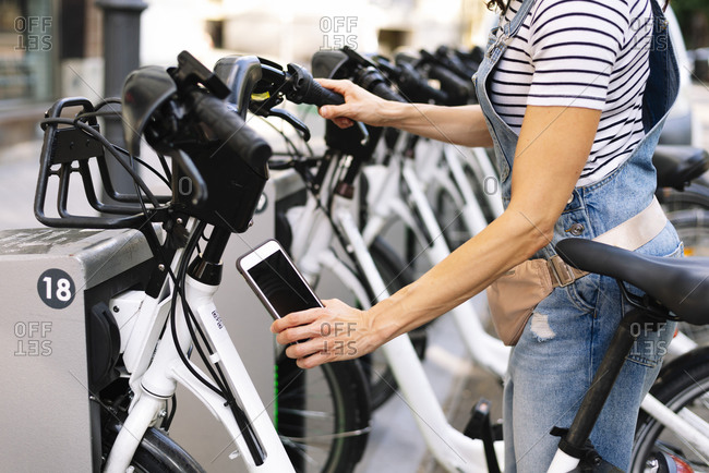 Midsection of woman scanning QR code on bicycle parking station