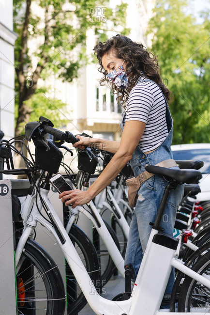 Woman scanning QR code on electric bicycle with smart phone in city