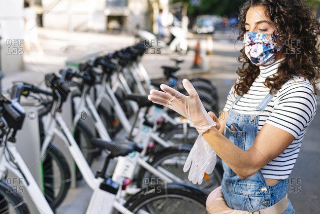 Mature woman wearing gloves at electric bicycle parking station during COVID-19