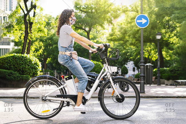 Woman riding electric bicycle on street during COVID-19