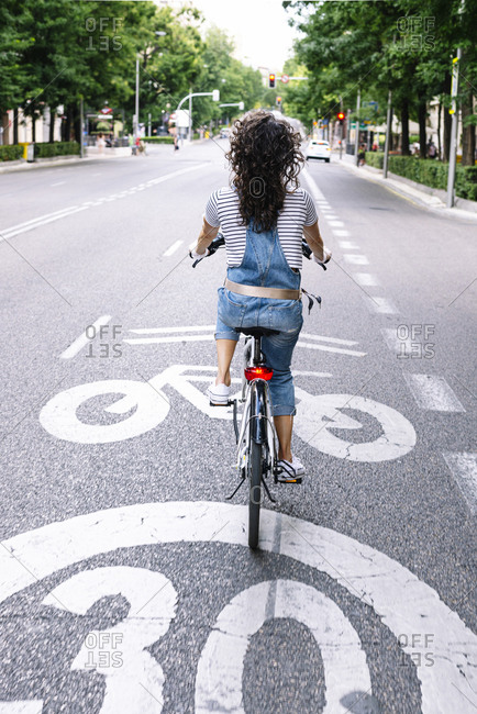 Woman riding electric bicycle on street in city