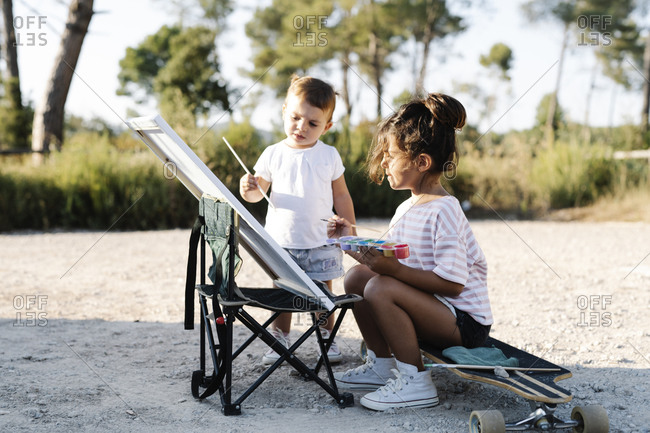 Baby girl painting with sister on canvas at park during sunset