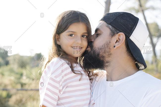 Mature man kissing cute daughter at park during sunset