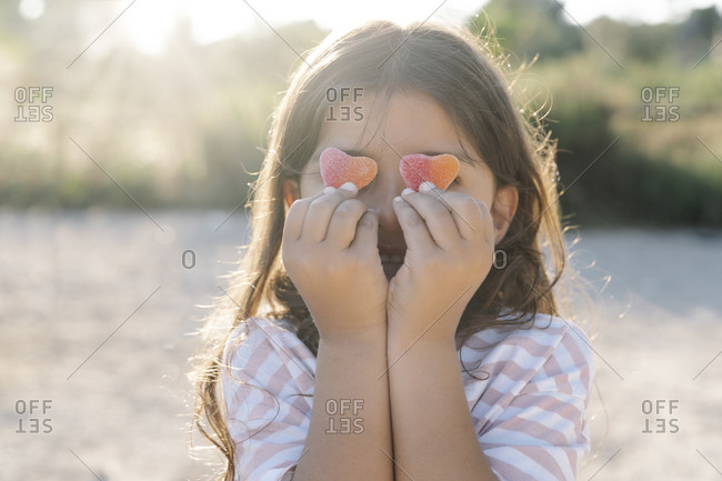 Close-up of cute girl holding candy hearts against face at park during sunset