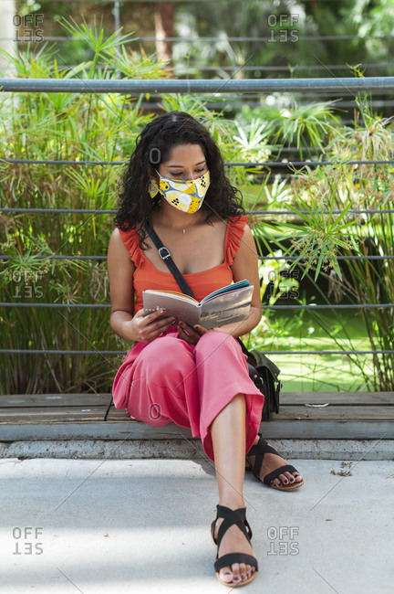 Young woman wearing protective mask while reading book sitting in park during COVID-19 pandemic