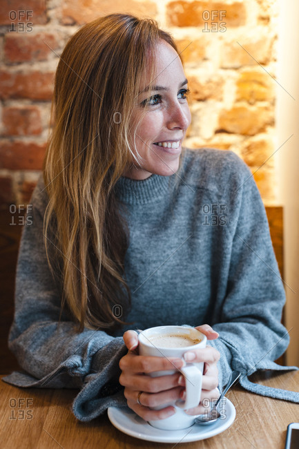 Smiling woman holding coffee cup at coffee shop