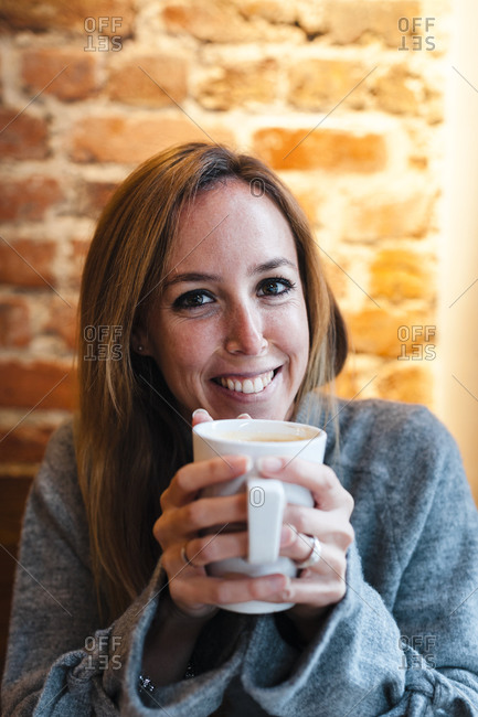 Woman smiling while holding coffee cup against brick wall at coffee shop