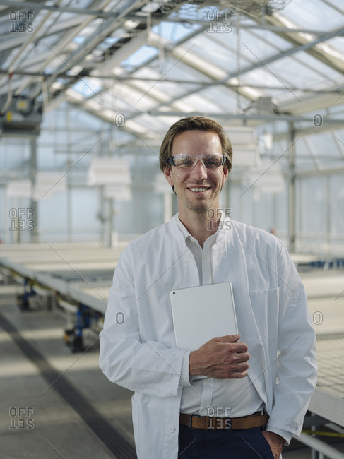 Portrait of a smiling scientist holding tablet in a greenhouse