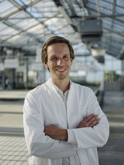Portrait of a smiling scientist in a greenhouse
