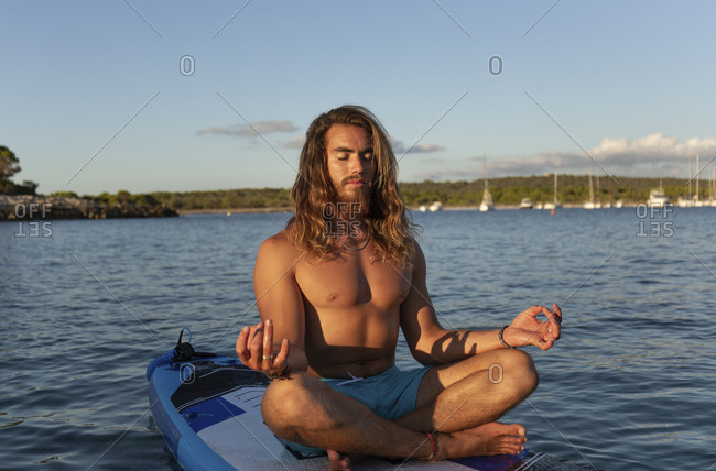 Young man with long hair meditating while sitting on paddleboard at sea against sky during sunset