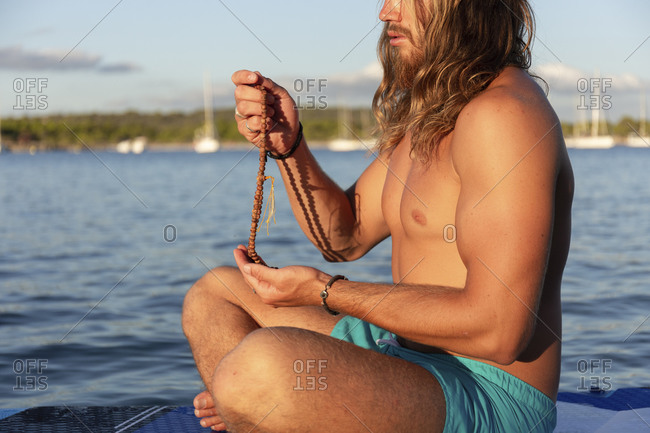 Shirtless man praying with rosary beads while sitting cross-legged on paddleboard at sea