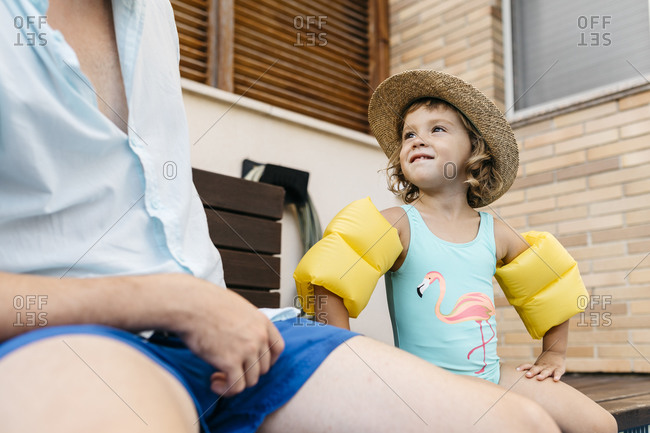 Little girl with her uncle sitting on poolside