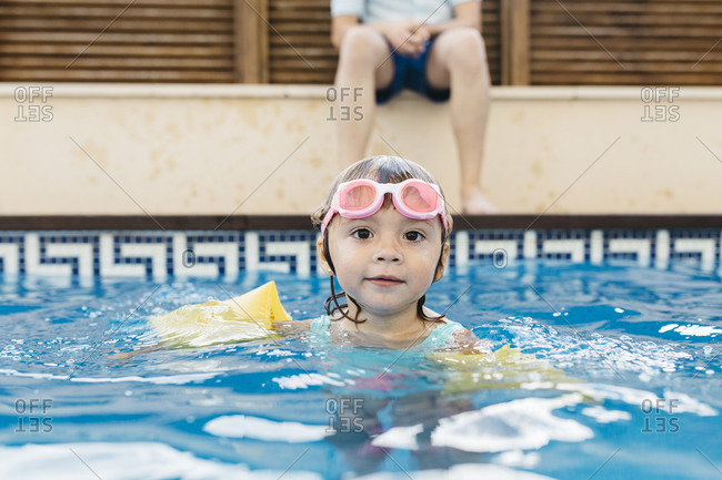 Little girl with swimming goggles in swimming pool
