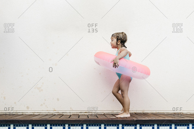Little girl with floating tire walking at pool edge