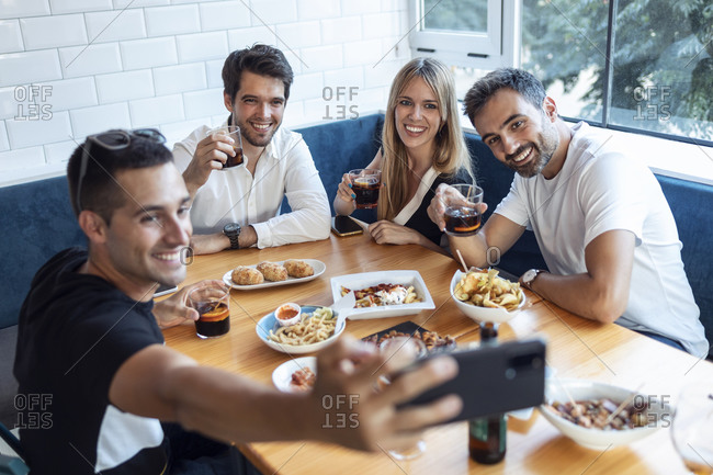 Group of friends taking selfie while having meal at restaurant