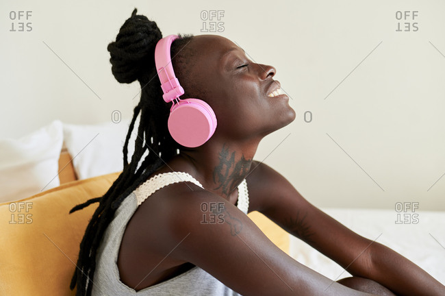 Beautiful woman listening music while sitting on bed at home