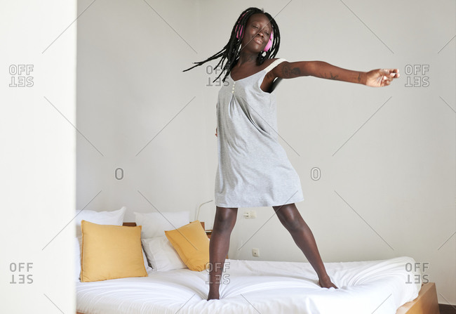 Carefree woman with arms outstretched standing on bed at home