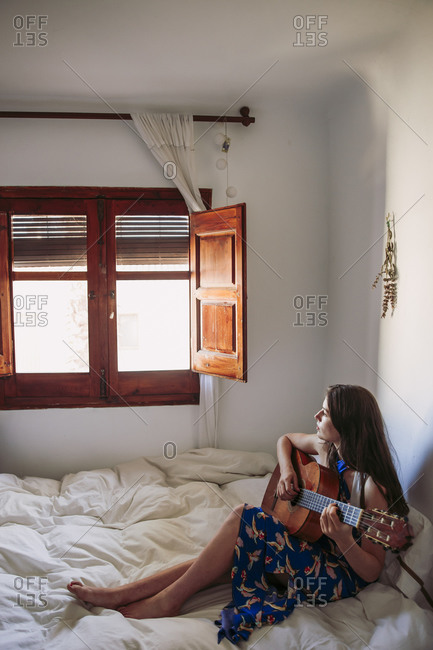 Woman looking through window while practicing guitar in bedroom at home