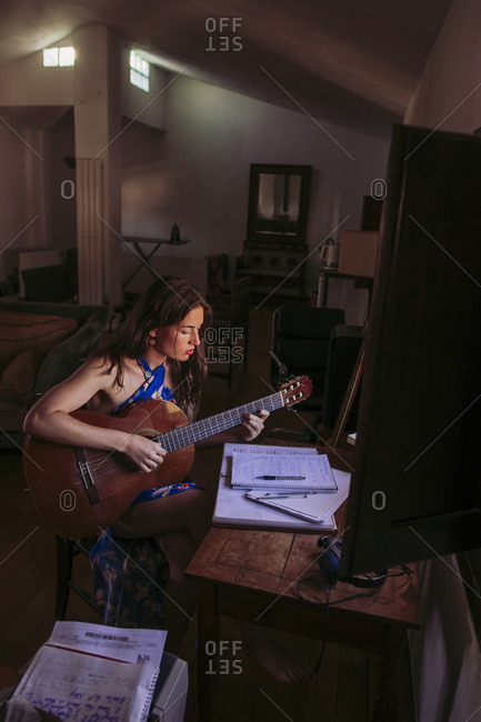 Young woman practicing guitar in living room at home