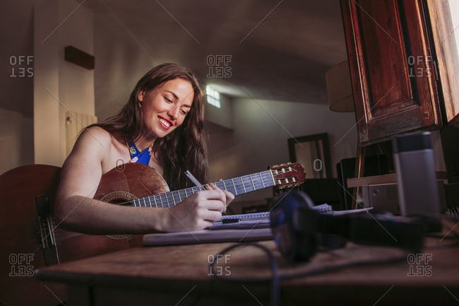 Smiling young woman writing in book while practicing guitar at home