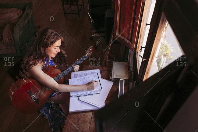 Young woman writing in book while practicing guitar at table in living room