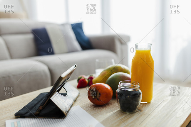 Digital phone kept by fruits and juice on table in living room at home