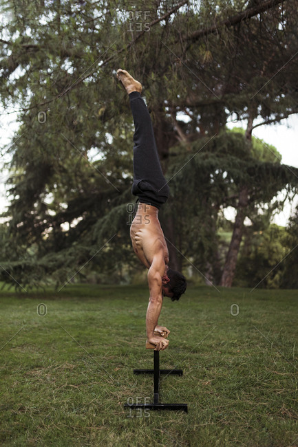 Male athlete practicing handstand on bench at park