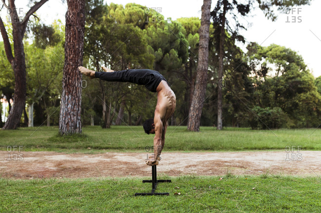 Shirtless male athlete practicing Acro yoga on bench at park
