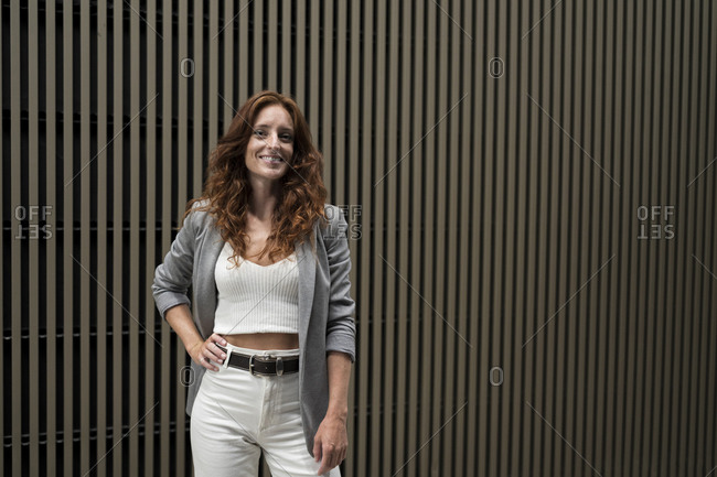 Smiling businesswoman with hand in hip standing against striped wall
