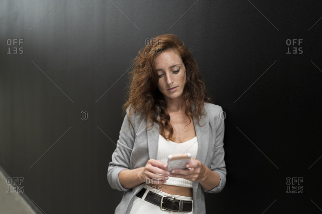 Businesswoman using smart phone while leaning on black wall in corridor