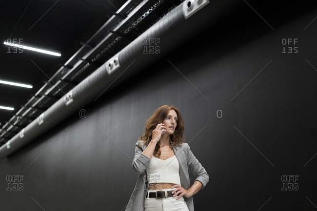 Beautiful businesswoman talking on smart phone while standing against black wall in corridor