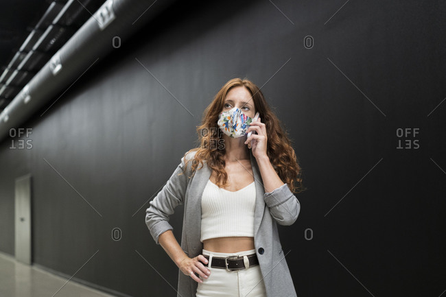 Businesswoman wearing protective mask while talking on smart phone against black wall in corridor