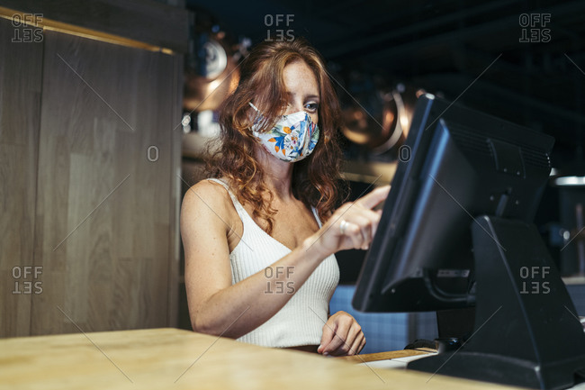 Waitress taking order with protective mask on face at restaurant