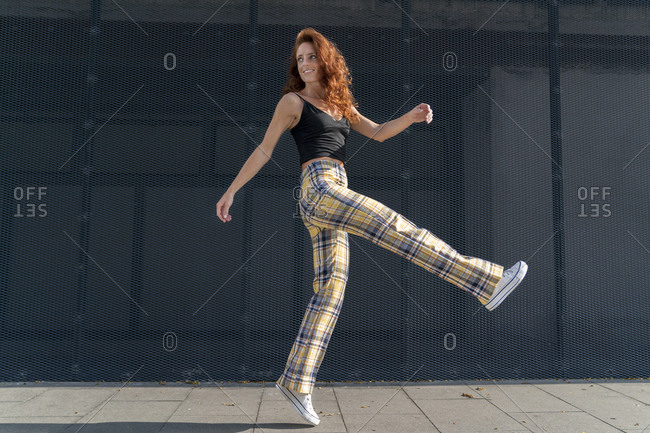 Smiling redhead woman jumping on sidewalk against fence