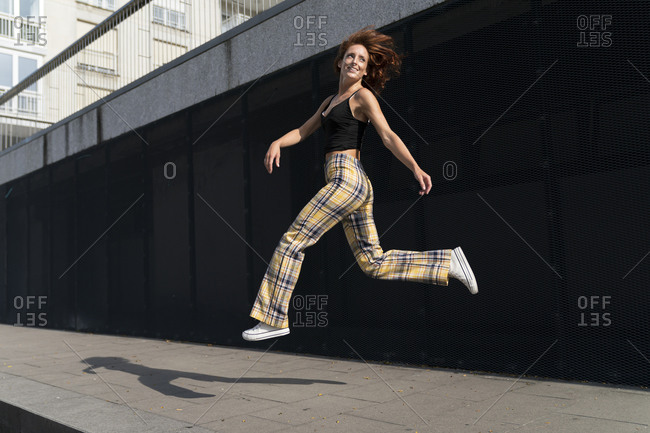 Cheerful woman with tousled hair jumping on sidewalk in city during sunny day