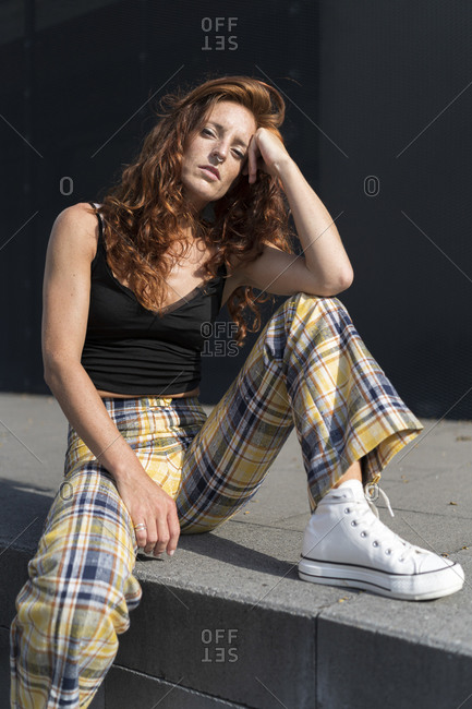 Redhead woman with head in hand sitting at sidewalk on sunny day
