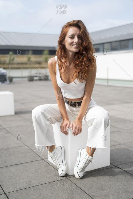 Beautiful redhead woman sitting on white cube