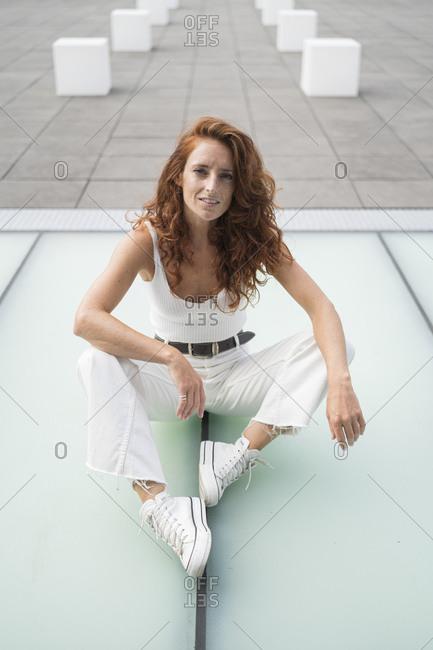 Redhead woman sitting on footpath