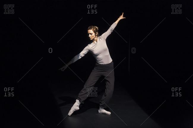 Female ballet dancer rehearsing on black stage