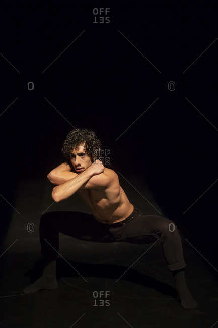 Male ballet dancer performing on black stage