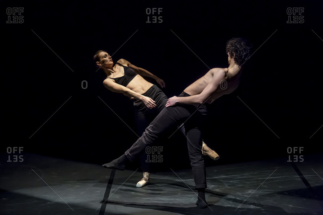 Male and female dancer performing contemporary ballet on black stage