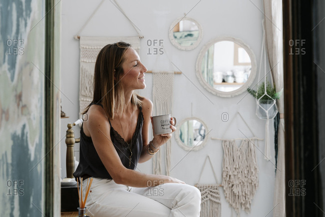Thoughtful smiling woman holding cup while sitting on table and looking away