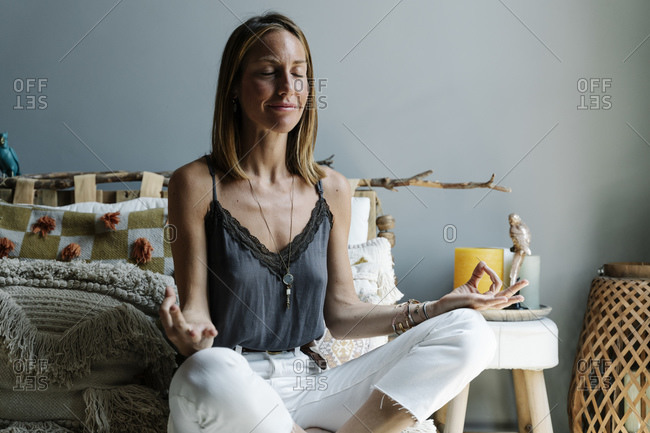 Beautiful woman meditating in lotus position with eyes closed