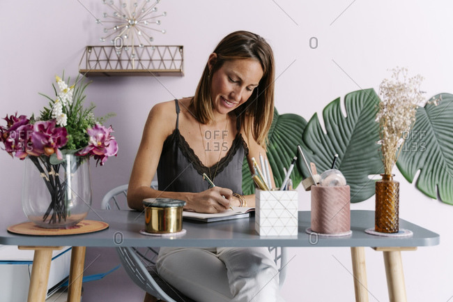Smiling woman writing in diary while sitting at table against wall