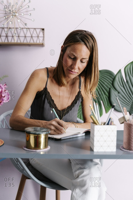 Woman writing in diary while sitting at table against wall