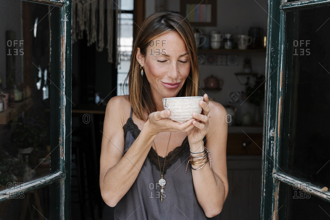 Smiling woman with eyes closed holding bowl of matcha tea at cafe
