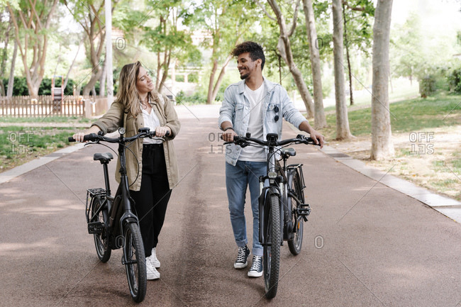 Smiling young couple with electric bicycles walking on road