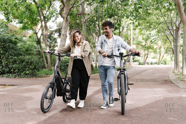 Smiling boyfriend and girlfriend walking with electric bicycles on road